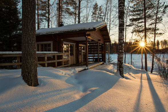Finland sauana house covered in snow during a bright day