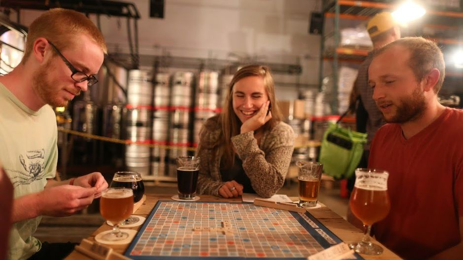 People drinking beer and playing scrabble