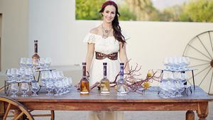 Woman standing in front of table with bottles of tequila.