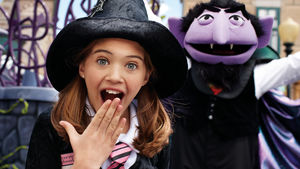 A yound girl dressed as a witch beside The Count from Sesame Street