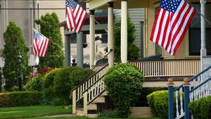 American flags fly patriotically on small town American city porches to celebrate a holiday.